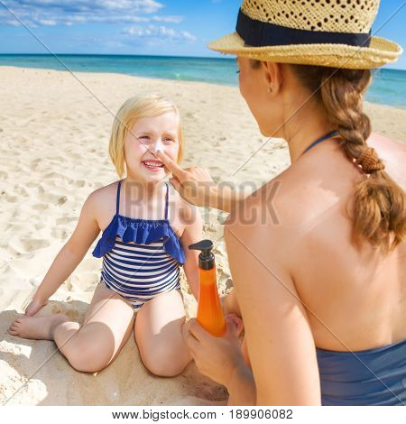 Happy Young Mother And Daughter On Seashore Applying Spf