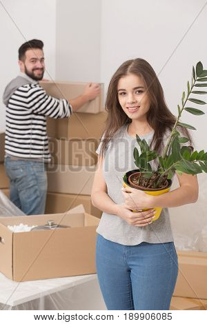 Happy young couple unpacking boxes and moving into a new home. Woman holding plant and smiling and man unpacking boxes.