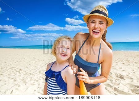 Happy Mother And Child On Seashore Applying Suntan Lotion