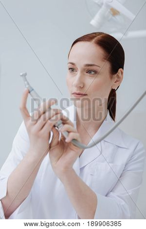 Special tool. Very attentive dentist wearing white smock keeping arms bent in elbows while looking forward