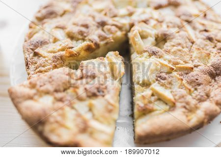Fresh baked apple pie on a white plate and a cut piece of pie on a light wooden background.