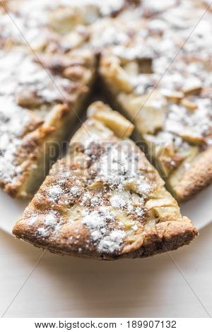 A fresh baked apple pie and a cut piece of pie are sprinkled with sugar and lie on a white plate on a light wooden background.