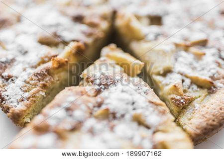 A fresh baked apple pie and a cut piece of pie are sprinkled with powdered sugar close-up view