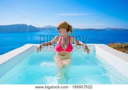 Woman relaxing in outdoor bathtub in pink bikini