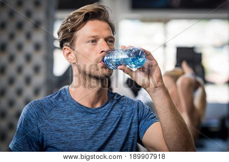 Young man drinking water after sports. Portrait of handsome muscular man drinking a bottle of water at gym. Sporty guy drinking mineral water after workout at the modern fitness centre.