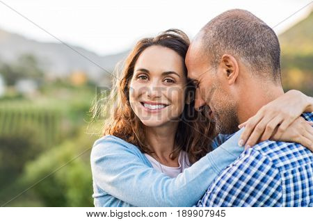 Mature romantic couple embracing outdoor. Happy woman embracing her multiethnic boyfriend at park during sunset. Smiling brunette woman in love with her husband looking at camera.