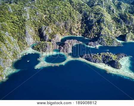 Aerial view of lagoons with boats surrounded by rocks and turquoise sea. Palawan
