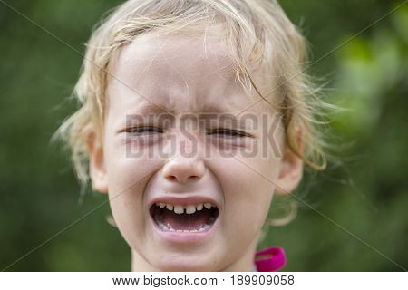 Beautiful sad little girl crying on summer background close up