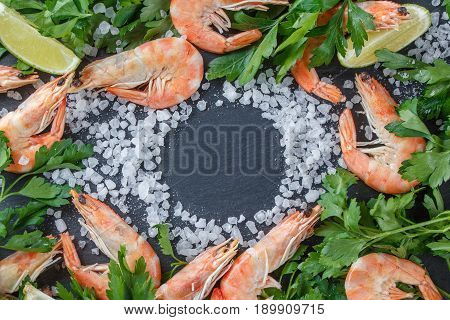 Shrimps With Lime, Herbs And Sea Salt On A Black Background. Frame For Your Text.