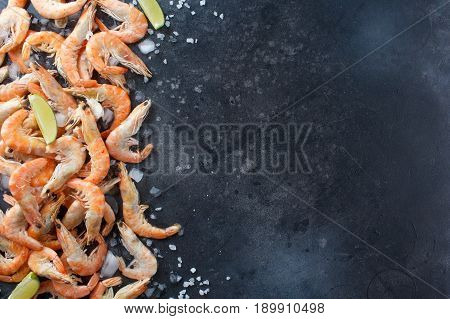 Shrimps With Lime, Ice And Sea Salt On A Black Background. Frame For Your Text. Shrimp With Lime And