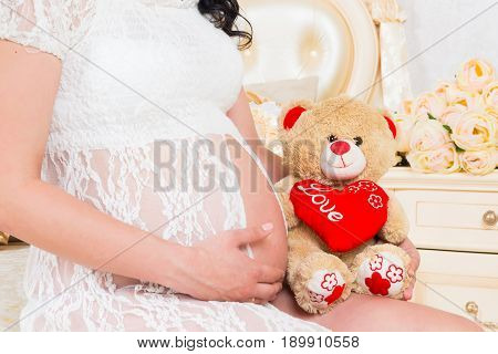 Pregnant in a white lace dress with teddy bear.