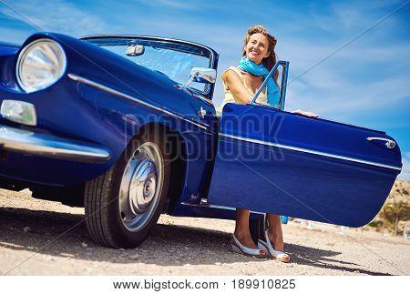 Beautiful woman sitting in retro cabriolet car