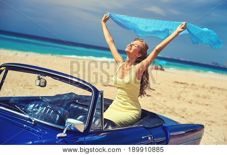 Happy woman with a hands raised sitting in retro cabriolet car on the beach near the turquoise sea. Idyllic scenery