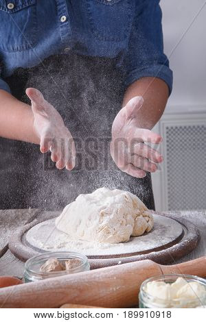 Baking concept, sprinkle flour on yeast dough. Flour, milk, and eggs on wooden cutting board, pastry ingredients. Cropped image of unrecognizable woman knead. Female baker closeup, vertical