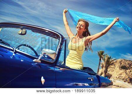 Happy woman with a hands raised sitting in retro cabriolet car