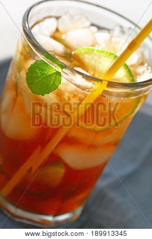 Closeup view of iced tea with lime and mint focus on condensation