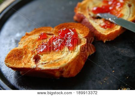 Spreading jam on brioche toast on a dark pan