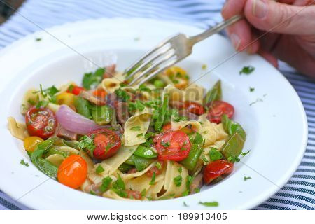 Bowl of noodles with cherry tomatoes and fresh peas with man's hand and fork outdoors