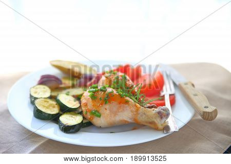 Plate of roast chicken legs zucchini fingerling potatoes and tomatoes with copy space