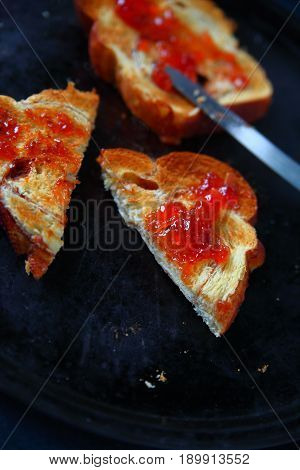 Slices of toast with raspberry jam one cut in half on a dark metal baking pan