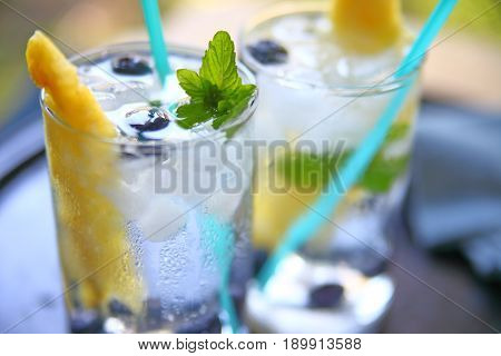 Glasses of white wine with fresh pineapple blueberries and mint with crushed ice