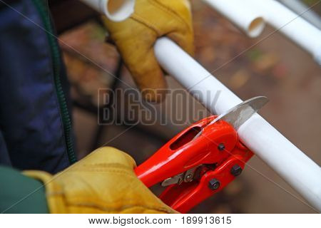 Worker with gloves uses tool to cut a length of PVC pipe