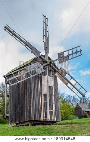 Ancient traditional wooden windmill beautiful spring landscape with sky. National architecture. Ancient traditional wooden windmill, beautiful spring landscape with sky. National architecture. National Museum Pirogovo in the outdoors near Kiev.