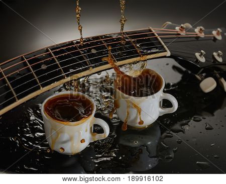 Concept acoustic guitar and two cups of coffee. Splash, streams flow over the fretboard of a guitar.