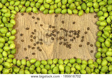 Picture frame made of green young walnuts in husks and inside several coffee bean on wooden table