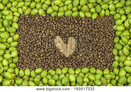 Picture frame made of green young walnuts in husks and inside a lot coffee bean with hert on wooden table