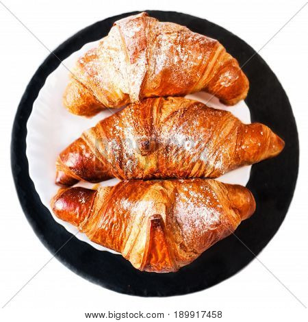 Fresh croissants on a plate isolated on white background close up. Tasty golden croissants macro