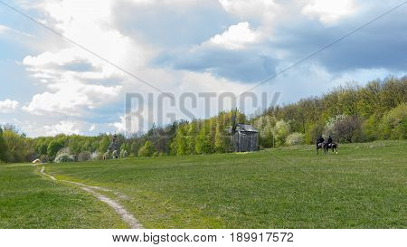 Ancient traditional wooden windmill and church beautiful spring rural landscape with horsemen.