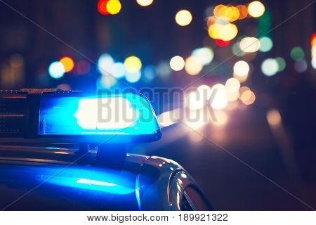 Danger on the road. Blue flasher on the police car at night.