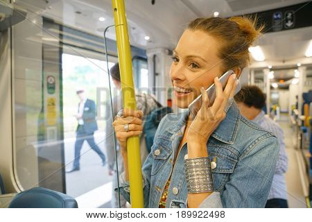 City girl standing in subway car and using smartphone
