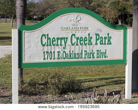Oakland Park FL USA - March 10 2017: Green white and yellow Cherry Creek Park sign outside on a sunny day. Cherry Creek Park in Oakland Park Florida one winter day