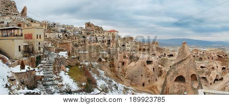 Panoramic view on ancient antique old volcanic ashs tuff calc sinter houses homes and hotels for tourists in Cappadocia Kapadokya Turkey. Holidays vacations tours. Famous sightseeing tours viewpoints