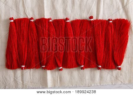 Red tassels line close up. Woman handicraft. Art, creativity, hobby, home workshop concept