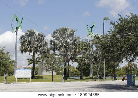 Fort Lauderdale FL USA - May 16 2017: Wind turbines and electric vehicle power charging station in Mills Pond Park. EV charging stations and urban wind turbines