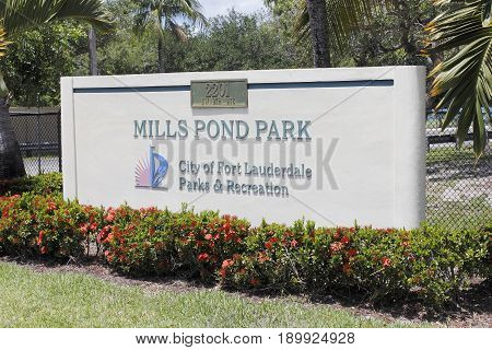 Fort Lauderdale FL USA - May 16 2017: Large entry signage with red flowers at the entrance to Mills Pond Park. Front sign in landscaped Mills Pond Park on a sunny day