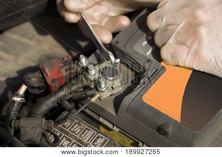 Battery clutch unscrewed by service technician. The hand of a mechanic with a flat key unscrews the battery in the car.