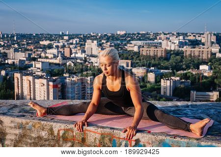 Portrait Of Blonde Strong Woman In Sportwear Doing Workout Stretching On The Roof Of Skyscraper Abov