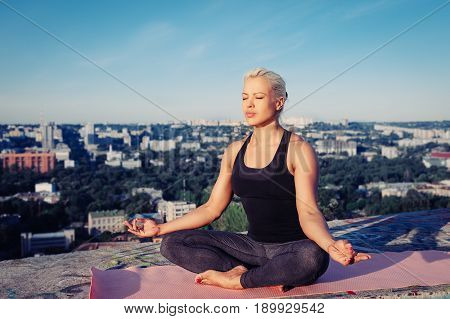 Portrait Of Beautiful Blonde Strong Woman In Sportwear Doing Workout On The Roof Of A Skyscraper Abo