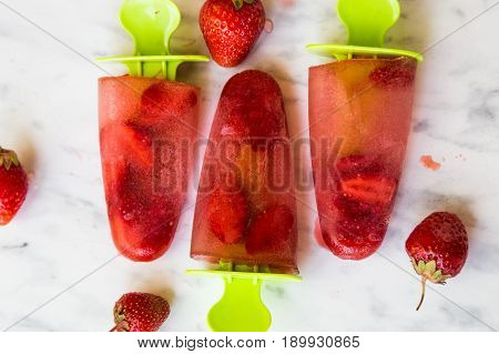 Summer dessert - frozen fruit. Fruit strawberry ice. Strawberry ice cream on a marble table.