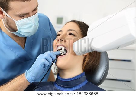 Dentist taking a teeth radiography to a patient in an office