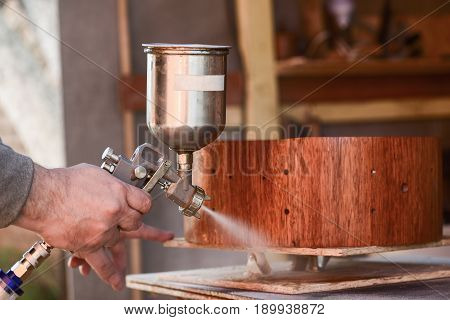Carpenter covering wooden drum with lacquer closeup