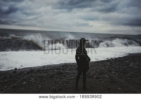 Woman dressed in a black coat on the beach during a storm