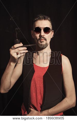 Portrait of a man smoking a pipe on a black background