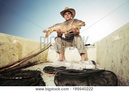 Fisherman holding a big carp on the river