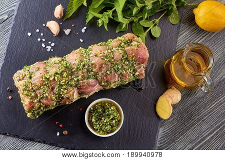 Marinated raw pork loin with spices on black stone plate. Ready for baking