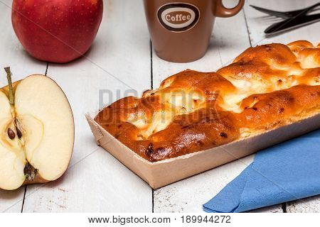 An elongated apple cake with coffee and Cutlery